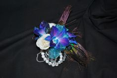 Wrist corsage featuring blue purple orchids, white tea roses and peacock feathers accented with blue ribbon- design by Leigh Florist - http://www.leighflorist.com  - #prom #prom2014 #promflowers #audubonprojectgraduation #promcorsage