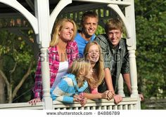 stock photo : happy family standing together in a gazebo in the park