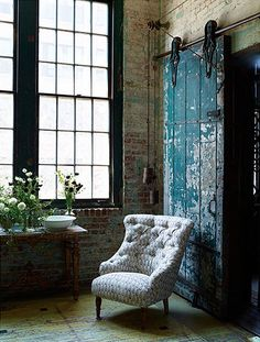 Teal paint on a barn door. Old brick walls. Tall ceiling. Black framed windows. Pretty tufted chair. Antique wood table. White porcelain bowl. Flowers in multiple vases. Beautiful!