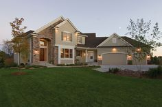 This European-influenced two-story home has stone accents and wide board siding.  European House Plan # 481034.