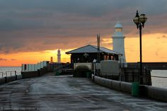 A Winter Sunrise on the Prince of Wales Pier, Dover Harbour, Kent, England, UK. Behind the frost-covered roof of the Harbour View Cafe is the Prince of Wales Pier Light. Built in 1902, this lighthouse is a 46-feet high stone tower with a very quick flashing green light (VQ, 100+ flashes per minute). To the left of the cafe is the distant Admiralty Pier Light, the Western Entrance, English Channel, and Cliffs of France. Port of Dover Tourism and Travel. See http://www.panoramio.com/photo/8475...