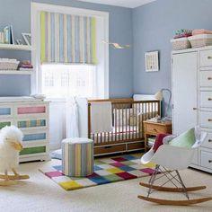 babyzimmer-tapete-blau-bunter-teppich-rollos-schaukelstuhl-holzbeine-plastiksitz-weißer-schrank