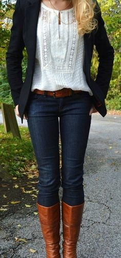white embroidered blouse, black blazer, jeans, & brown boots.