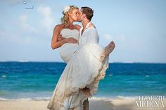 bride in groom's arms with clear blue waters