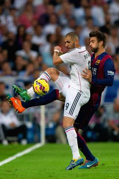 Gerard Pique of Barcelona and Karim Benzema of Real Madrid CF battle for the ball during the La Liga match between Real Madrid CF and FC Barcelona at Estadio Santiago Bernabeu on October 25, 2014 in Madrid, Spain.