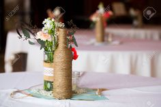 28003092-DIY-wedding-decor-table-centerpieces-with-wine-bottles-wrapped-in-burlap-twine-and-rose-flowers--Stock-Photo.jpg (1300×866)