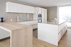 Die Küche Siematic S2 mit mit Lackfronten harmoniert mit dem Bodenbelag und der integierten Theke aus massivem Holz.