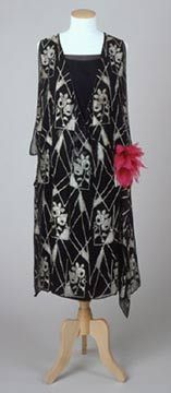 1925 Evening dress; vening dress of black silk crepe with wide scooped neckline. Separate under-slip of plain black silk.  Bodice and skirt almost completely covered with applied black plastic sequins and glass bugle beads. Wide, open-seamed sleeves, weighted with tassels of bugle beads.