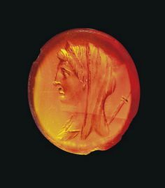 A ROMAN CARNELIAN INTAGLIO RINGSTONE CIRCA 1ST CENTURY A.D. The flat oval stone engraved with a female head, wearing diadem and himation drawn over head