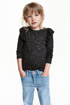 Top met volants: Een tricot T-shirt met lange mouwen en een volant op de schouders.