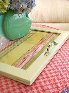 Picture frame serving tray. Remove the glass of a large frame. Paint the frame in your desired color. Attach drawer pulls to the short sides of the frame as handles. Insert a piece of pretty fabric or decorative paper behind the glass.