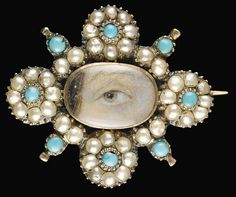 Yellow gold brooch with border of thirty-two natural oriental half pearls in a floral motif with eight small turquoise stones; oval locket back with woven brown hair under glass, circa 1820. Brown right eye. Purchased from Edith Weber, New York. Dimensions: 1 by 1-1³8 by 1³4 inch. Photo by: M. Sean Pathasema.