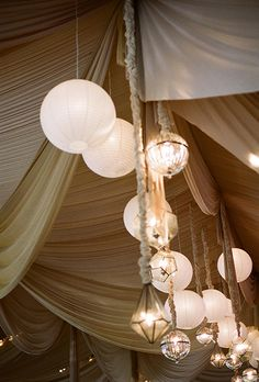 Brides.com: . Paper lanterns interject some fun into a refined ceiling of elegant taupe drapery, classy spherical-shaped lanterns, and diamond-shaped pendants made of glass.