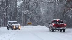 Traffic negotiates the turn at Menchville Road and Lucas Creek Road early Thursday. Snow-packed roads challenged drivers who ventured out. (Photo by Adrin Snider / Daily Press)