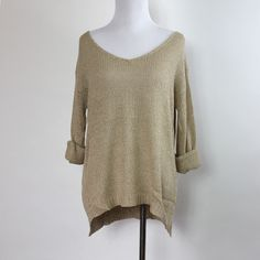 This lovely beige sweater has a wide scoop neck and subtle high/low design.Keep it casual with distressed cutoffs, or pair it with leggings.  Approx. measurements from a Size SMALL  (Add an inch for next size up)  Length: 25 inches  Bust: 38 inches 80% Cotton, 15% Acrylic 5% Nylon