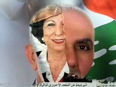 The picture of a female candidate for Beirut's municipal elections appears under a teared picture of a male candidate on a wall in Beirut. (PATRICK BAZ / AFP)