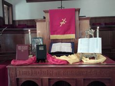 The Altar table on Pentecost Sunday: Bibles, prayerbooks, and hymnals in other languages. The Holy Spirit reaches out to people in every place and time.