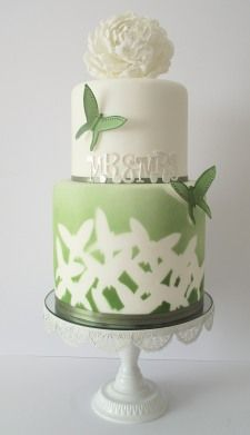 Green painted wedding cake using stencils and an airbrush to showcase butterflies. Includes sugarpaste butterflies and a single white flower for the topper. ( what a lovely idea!)