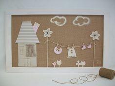Cuadro infantil de ropa tendida con casita. | Cuadro infantil con fondo de tela de rafia marrón, con detalle de ropa tendida, casita, nubes y flores. MEDIDAS:76x46