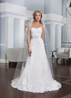 Lillian West Style 6334 is an organza slim A-line gown with sweetheart neckline. The natural  waist is accented with a detachable satin ribbon and the back is finished with organza covered buttons that extend to the end of the  chapel length train.