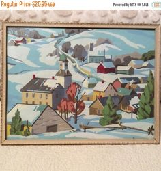 This is a winter village scene done in paint by number. It is in a wooden frame with glass. It was probably painted in the 1960s by hand. I