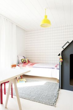 A brightly lit, neutral colored children's bedroom with a harlequin patterned accent wall.