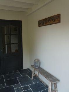 Landelijke hal met oude bank en kapstok - zwarte deur