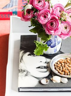 An arrangement of seemingly disparate objects—scattered shells, a book of fashion photographs—comes together on an oversize lacquer tray. Pink ranunculus, one of Kate's favorite flowers, are a common fixture throughout the apartment.
