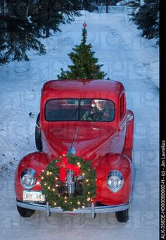Man driving a vintage 1941 Ford pickup with a Christmas wreath on the grill and a tree in the back during Winter in Southcentral, Alaska