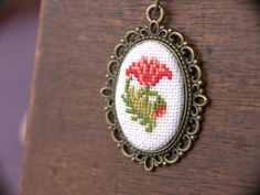 Items similar to Cross stitch pendant necklace - Carnation - Coral Red with Antique Brass Setting Color, mm Round on Etsy Beaded Embroidery, Cross Stitch Embroidery, Cross Stitch Patterns, Hand Embroidery Design Patterns, Small Cross Stitch, Palestinian Embroidery, Carnations, Minis, Clothing Accessories