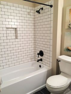 Classic Guest Bath by BlankSpace LLC, Pittsburgh PA. Custom Tub/Shower Surround with Matte White Subway Tile & Espresso Grout; Shower Niche; Oil Rubbed Bronze Accents #tilebathtub #smallbathroomrenovations