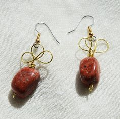 These earrings feature a really pretty red stone bead and brass coloured wire designs!