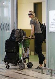 Doing it herself: Maria was spotted pushing her own luggage into the arrivals gate and sho...