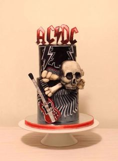 ACDC themed birthday cake. Modeling chocolate letters on top, skull, and guitar. Fondant hand cut pattern on bottom tier, and hand painted top tier. TFL :)
