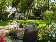 """Everything we need in the backyard: a perfect little playhouse--lots of grass to play football on--flowers and lots of outdoor seating. """"Go play, girls! Daddy and I are opening a bottle of wine!"""""""