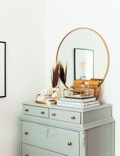 commode vintage et coiffeuse vert gris céladon, pile de livres, miroir rond dans cadre doré, produits de toilette, mur blanc