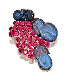 SAPPHIRE AND RUBY BROOCH, SUZANNE BELPERRON, 1950S.  The brooch of foliate inspiration designed as a stylised bunch of leaves and fruits, set with carved sapphires, circular-cut and oval rubies, mounted in yellow gold,  French assay and maker's marks. [This came very close to being put on the Fugly board. Very, very close.]