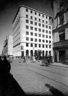 Przedwojenna centrala Pocztowej Kasy Oszczędności (PKO). Jej obłożony kamiennymi płytami nowoczesny gmach stanął tuż przed wybuchem II wojny światowej na rogu Świętokrzyskiej i Marszałkowskiej. Budynek zniszczony został w 1944 r., a jego szkielet stał do lat 60. Obecnie w jego miejscu jest pusty placyk przed restauracją McDonald's. Na zdjęciu widok ulicy Świętokrzyskiej w kierunku Nowego Światu. Pierwsza poprzeczna ulica to Marszałkowska.