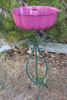 bundt pan and wrought iron candle holder converted to a super cute bird feeder.  I love how the bundt pan looks like a flower!  This would look super cute among your flower beds!