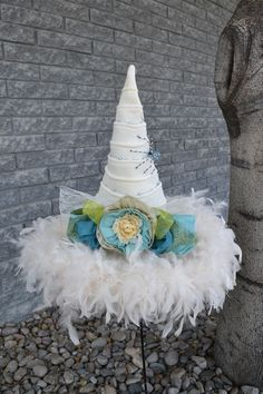 Be a cool and fresh witch this year in this cream colored hat dressed up in shades of blue and green. Cream Ridged Velvet 19 inch brim; 19 inch tall. Adjustable inner sizing band.