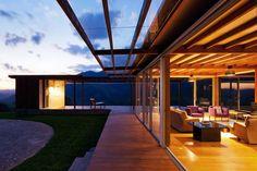 Entre o bloco da sauna e o ambiente de estar, a varanda aberta e integrada à natureza. Como extensão da área social, um deck protegido pela continuação da cobertura, com fechamento de placa de policarbonato