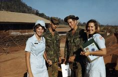 Two U.S. Army soldiers pose next to Red Cross nurses at a military base in Vietnam.