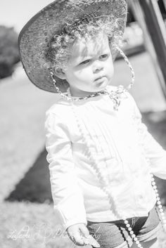 I LOVE her in the cowgirl hat and the pearls around her neck!