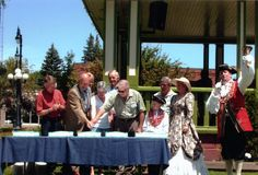 Cutting the cake at the Centennial Birthday Bash in Memorial Park in July 2008 are MPP Norm Miller, Bracebridge Mayor Don Coates, Chief Librarian Cathryn Rodney, author Patrick Boyer (in background), Library Board Chair Bob Taylor.