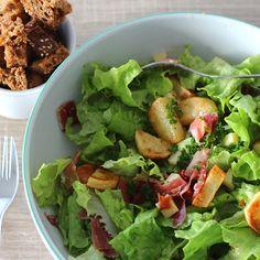Illustration Salade de Jambon Serrano & Pommes de Terre  Les ingrédients ... ... pour 2 personnes Pour les croûtons : 2 tranches épaisses de pain (rassi ou non - ici du pain aux céréales) - 2CS d'huile d'olive - Sel - Poivre // Pour les pommes de terre : 3 petites pommes de terre (ici des Mona Lisa) - 2CS d'huile d'olive - Sel - Poivre // Pour la salade : 1/3 salade batavia - 100g de Jambon Serrano - 60g d'emmental - 4 pétales de tomates séchées // Pour la sauce : 1CS bombée de moutarde à…