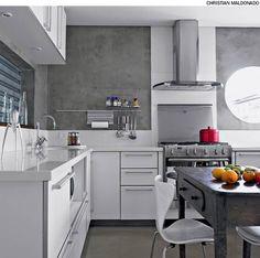O acabamento de cimento queimado está no piso e também nas paredes da cozinha, projetada pela arquiteta Claudia Haguiara. Para reforçar o aspecto industrial do ambiente, ela colocou, para fechar o passa-prato, uma janela de enrolar feita de chapa de ferro galvanizado, igual de lojas.
