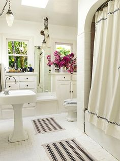 A few calculated details, such as the Moroccan-style pendants and a graphic shower curtain and mats, add a layer of relaxed character to this Spanish-style bathroom.