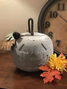Halloween/Fall pumpkin. Filled plastic pumpkin with quick-drying cement. Stick piece of rebar in as stem. Metal leaves & acorn bell cut off sale door hanger - $1 each. Turn around to plain side after Halloween. Super easy. Minimal mess. High impact.