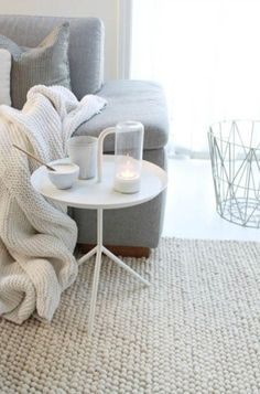 A cosy sofa with knitted rug and throw.