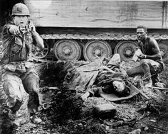During an ambush by the VC, an officer shouts orders as a wounded American soldier awaits evacuation near Saigon during the Vietnam War, 1969.